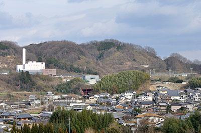 建設が進むやまと広域環境衛生事務組合のごみ焼却場(左)と受け入れた地域の町並み=2017年1月12日、御所市